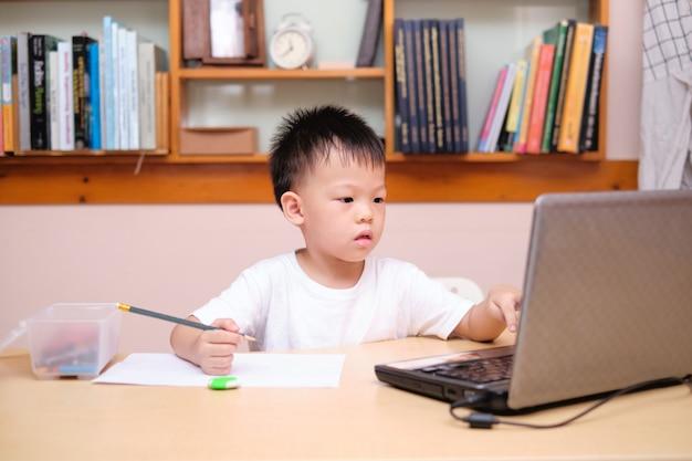 Aziatisch schooljongenjong geitje die laptop computer met behulp van die tijdens zijn online les thuis bestuderen, afstandsonderwijs, homeschooling concept