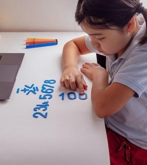 Aziatisch schoolmeisje dat huiswerk wiskunde bestudeert tijdens haar online les thuis met laptop thuis. nieuw normaal. covid-19 coronavirus. social distancing. blijf thuis
