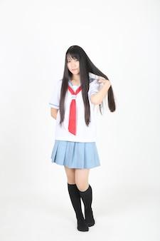 Aziatisch schoolmeisje dat op witte achtergrond wordt geïsoleerd