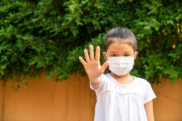 Aziatisch schoolmeisje draagt medisch masker toont stopbordhand voor corona, covid 19-virus