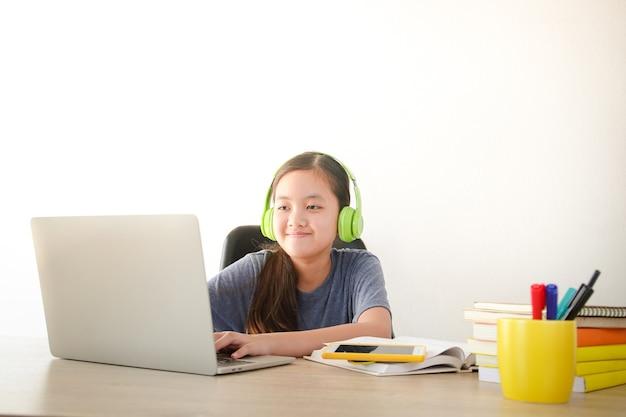 Aziatisch schoolmeisje leer online vanuit huis via videogesprekken. een laptop gebruiken om met docenten te communiceren. concept van online onderwijs. social distancing om de verspreiding van het coronavirus te verminderen.