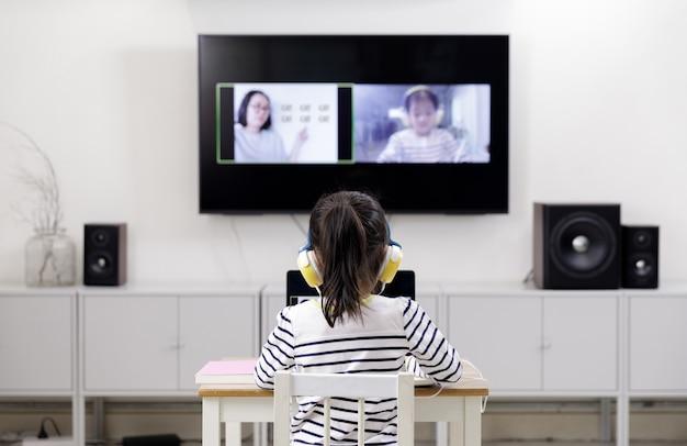 Aziatisch schoolmeisje leert thuis met laptop via videogesprek met haar leraar, sociale afstand tijdens quarantaine-isolatie tijdens de coronavirus (covid-19) gezondheidszorg