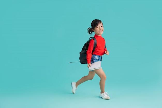 Aziatisch schoolmeisje loop naar school. in de achtergrondstudio