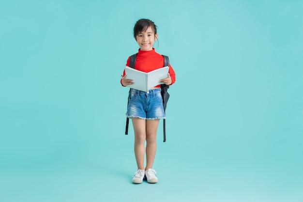 Aziatisch schoolmeisje opent ze het boek. in de achtergrondstudio