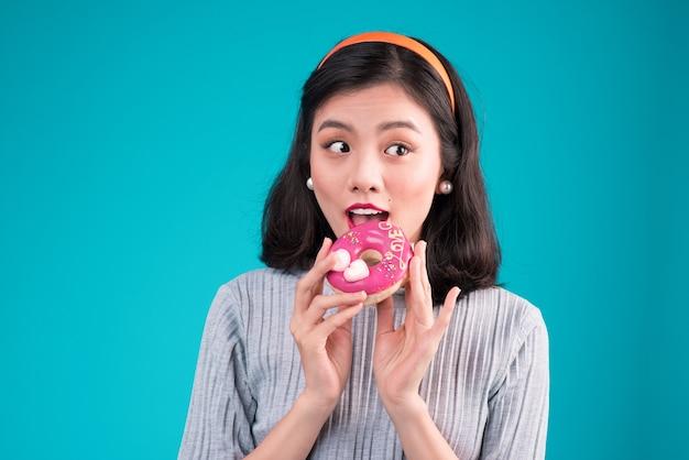 Aziatisch schoonheidsmeisje die roze doughnut houden. retro vrolijke vrouw met snoep, dessert staande over blauwe achtergrond.