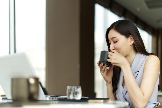 Aziatisch slim mooi meisje die een rust spreken door kop van koffiezitting te drinken in koffiewinkel.