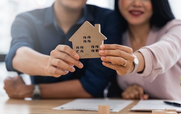 Aziatisch stel dat hun nieuwe huismodel presenteert nadat ze hun huiscontract hebben afgerond