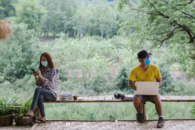 Aziatisch stel sociale afstand nemen en het dragen van beschermende maskers werken, coronavirus covid-19 ziektebescherming. gesprek vanaf een veilige afstand. beperking van socialisatie.