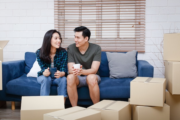 Aziatisch stel zit op een bank en is net verhuisd naar een nieuw huis om een warm gezin te stichten.