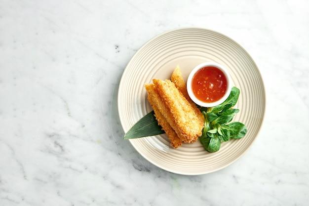 Aziatisch straatvoedsel - gefrituurde loempia in rijstpapier geserveerd in een beige bord met pittige chilisaus op een marmeren tafel. restaurant eten.