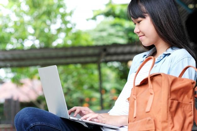 Aziatisch studentenmeisje die laptop computer, online onderwijs met behulp van