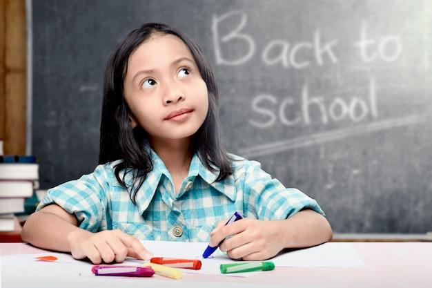 Aziatisch studentenmeisje die op witboek met kleurrijke kleurpotloden in het klaslokaal trekken