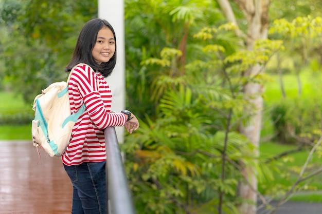 Aziatisch studentenmeisje die zich in het schoolpark bevinden in een zonnige de zomerdag