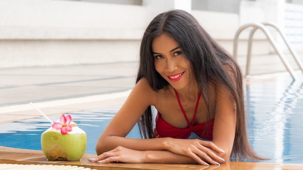 Aziatisch thais meisje sexy in rode bikini van het manierondergoed zit bij het zwembad met drankkokosnoot.