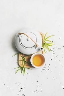 Aziatisch theeconcept met theestel op bamboemat die met droge groene thee wordt omringd