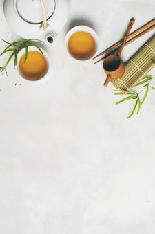 Aziatisch theeconcept, twee witte kop theeën, theepot, theestel, eetstokjes, bamboemat die met droge groene thee op witte achtergrond met exemplaarruimte wordt omringd. thee zetten en drinken.