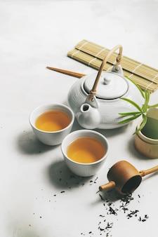 Aziatisch theeconcept, twee witte kop theeën, theepot, theestel, eetstokjes, bamboemat die met droge groene thee wordt omringd