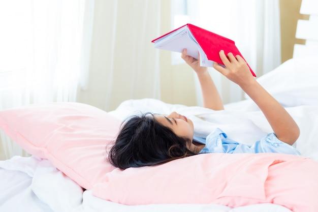 Aziatisch tiener vrouwelijk gelezen agendaboek op het bed