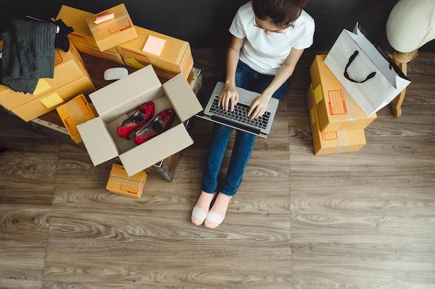 Aziatisch tienerbedrijfs bedrijfsvrouwenwerk thuis voor online het winkelen en verkoop.
