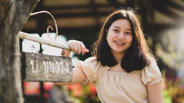 Aziatisch tienermeisje dat naar de camera kijkt en gelukkig glimlacht terwijl ze in de natuur reist.