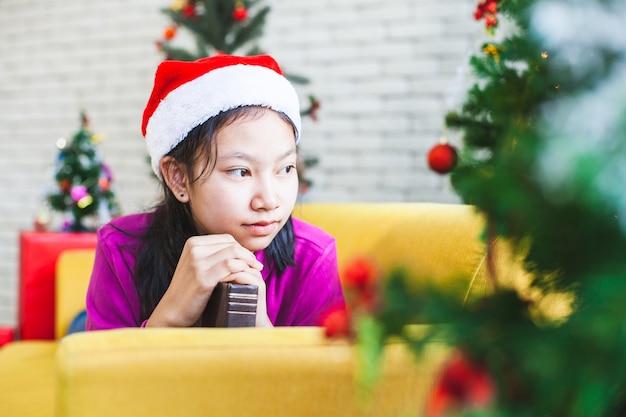 Aziatisch tienermeisje die handen maken die in gebed worden gevouwen om in kerstmisviering te wensen