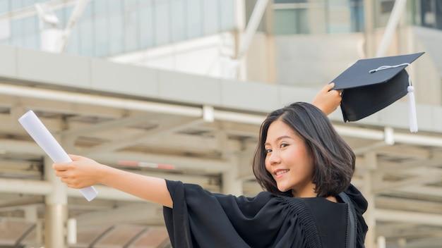 Aziatisch tienermeisje met afstuderen toga doek met gelukkig gevoel