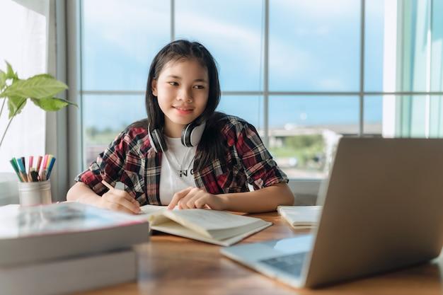Aziatisch tienermeisje met koptelefoon die online taal leert, laptop gebruikt, naar het scherm kijkt, thuis schooltaken doet, notities schrijft, naar lezing of muziek luistert, onderwijs op afstand
