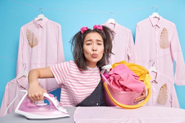 Aziatisch tienermeisje met twee paardenstaarten houdt lippen rond en houdt emmer vol wasgoed bezig met thuis strijken blauwe muur blue