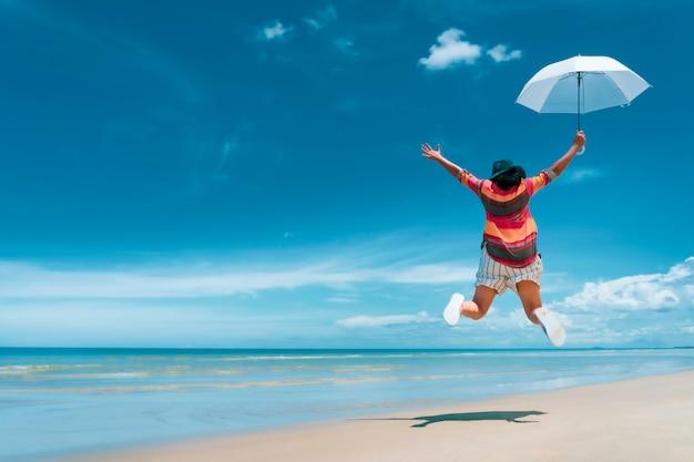 Aziatisch toeristenmeisje die op wit zandstrand springen met turkooise blauwe overzees in de zomerdag