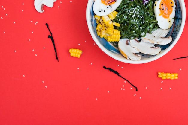 Aziatisch traditioneel voedsel in kom op rode achtergrond