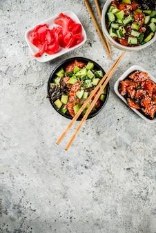 Aziatisch trendy eten, sushi por kom met komkommer, zalm, avocado, zwart-witte sesamzaadjes