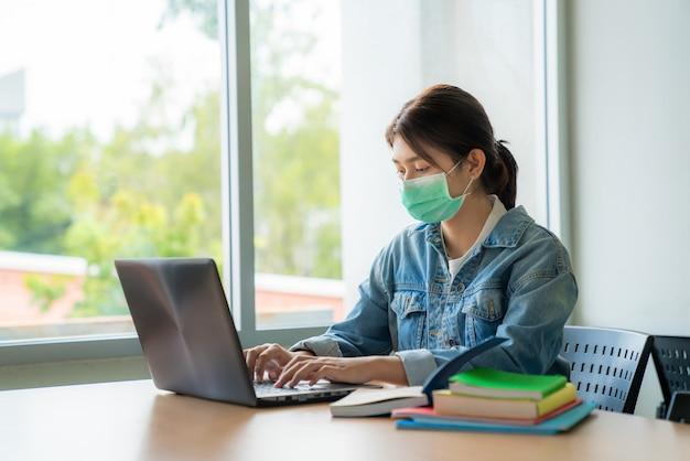 Aziatisch universitair studentenmeisje dat gezichts beschermend medisch masker draagt voor bescherming
