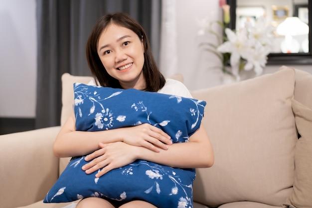 Aziatisch verblijf en ontspan in de woonkamer en kijk naar televisie (tv) tijdens de quarantaineperiode.