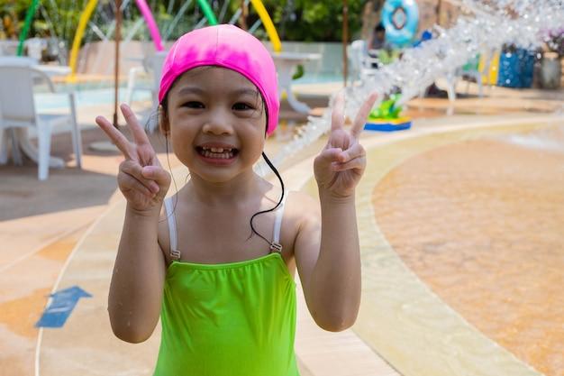 Aziatisch vierjarig meisje in zwembad dat vredestekens doet