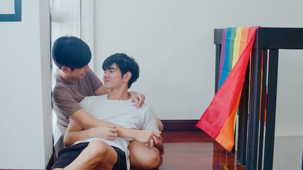 Aziatisch vrolijk paar dat en op de vloer thuis ligt koestert. jonge aziatische lgbtq + mannen kussen gelukkig ontspannen rust samen doorbrengen romantische tijd in woonkamer met regenboogvlag in modern huis in de ochtend.