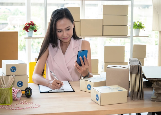 Aziatisch vrouw het schrijven adres op pakketdoos en het controleren van productorde op smartphone