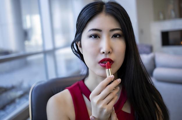 Aziatisch vrouwelijk model draagt een modieuze sexy rode jurk