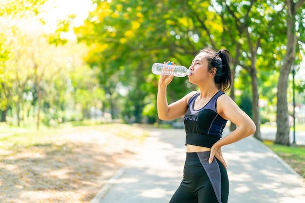 Aziatisch vrouwen drinkwater in sportwear