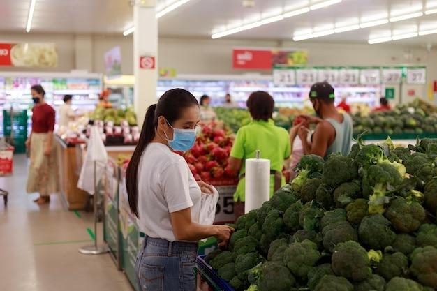 Aziatisch vrouwen lang haar die beschermend gezichtsmasker dragen in supermarkt warenhuis
