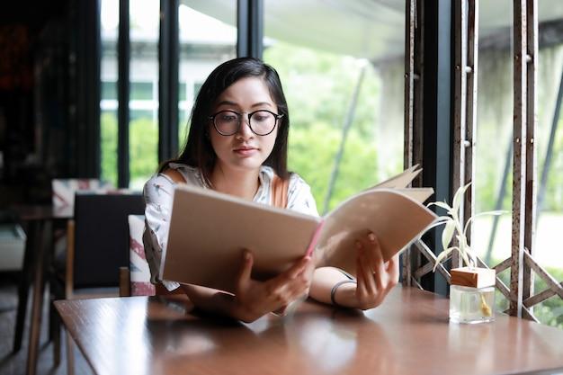 Aziatisch vrouwen open menu voor het opdracht geven tot in koffie en restaurant en het glimlachen voor gelukkige tijd