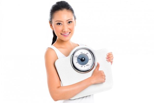 Aziatisch vrouwen verliezend gewicht met schaal
