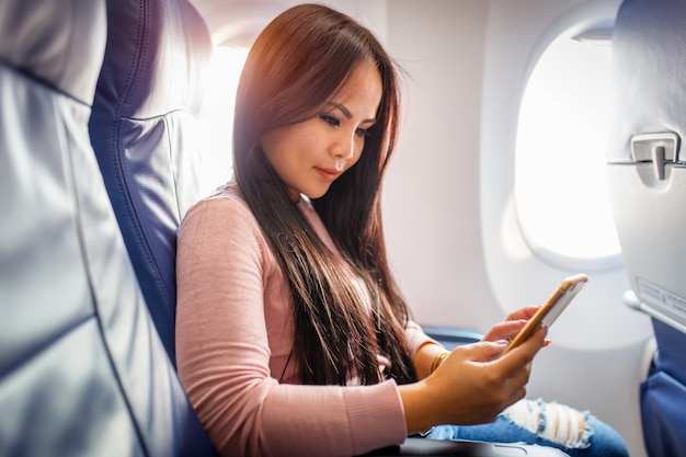 Aziatisch vrouwengebruik van mobiele telefoon binnen vliegtuig