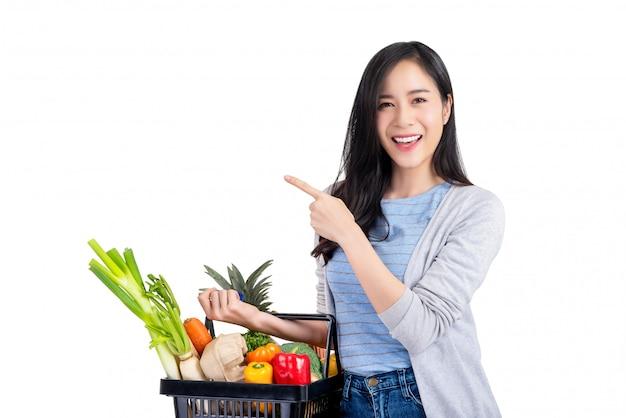 Aziatisch vrouwenholding het winkelen mandhoogtepunt van groenten en kruidenierswinkels