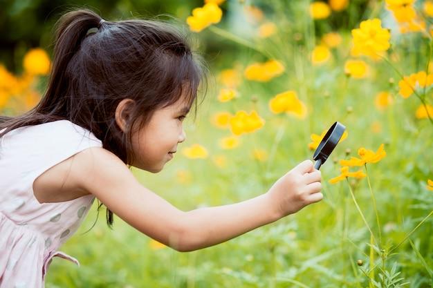 Aziatisch weinig kindmeisje die door een vergrootglas op kosmosbloem kijken in de tuin