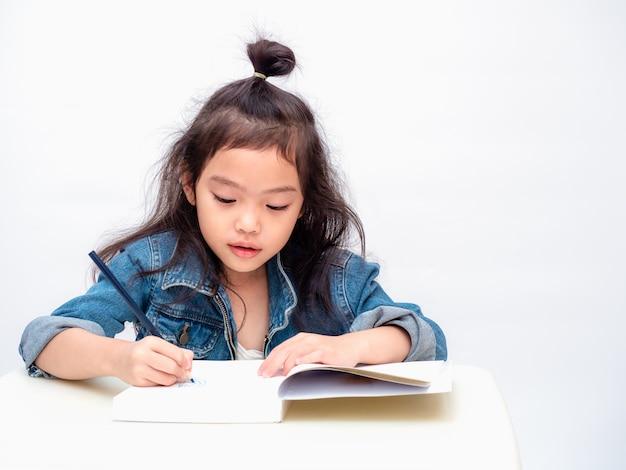 Aziatisch weinig leuk de kleurenpotlood van het meisjesgebruik en tekeningsbeeldverhaal op notitieboekje.