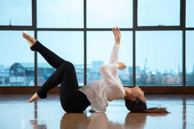 Aziatisch wijfje dat op vloer ligt terwijl het dansen