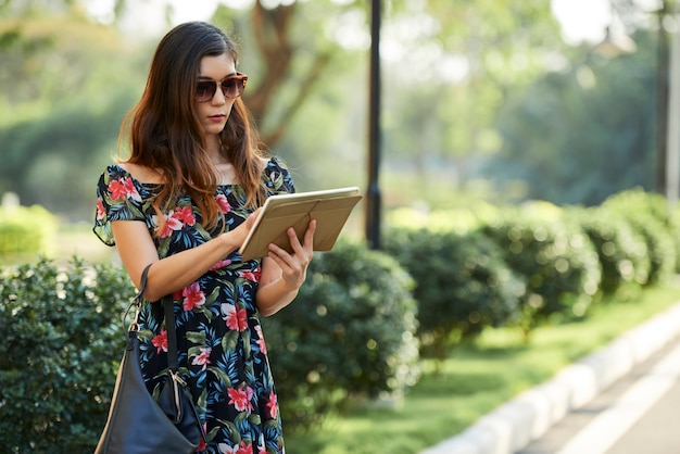 Aziatisch wijfje die tablet gebruiken dichtbij struiken