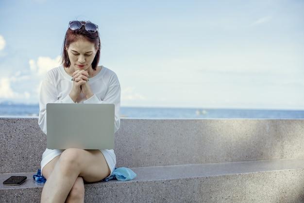 Aziatisch wijfje die tot god voor laptop bidden die openlucht werkt.