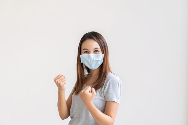 Aziatisch wijfje in gezichtsmasker op witte achtergrond die dient vuisten op te heffen en met geluk te schreeuwen.