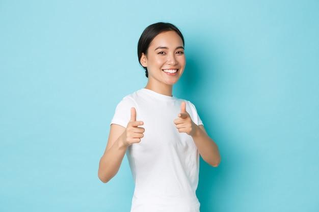 Aziatisch wijfje in het toevallige t-shirt stellen